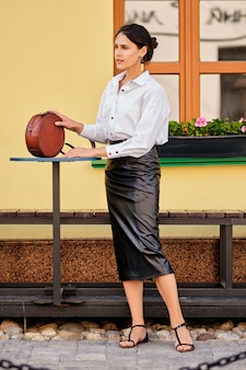 City portrait of elegant lady in leather skirt and white shirt with leather hand bag
