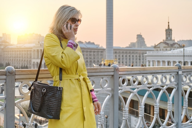 City portrait of mature smiling woman in yellow coat talking on mobile phone