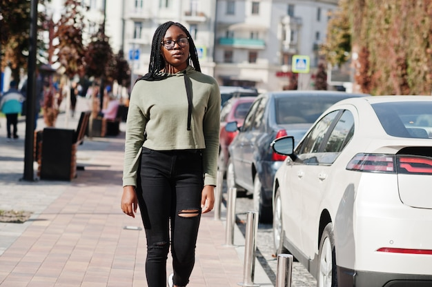 緑のパーカーと駐車場を歩いて眼鏡を身に着けている肯定的な若い暗い肌の女性の街の肖像画。