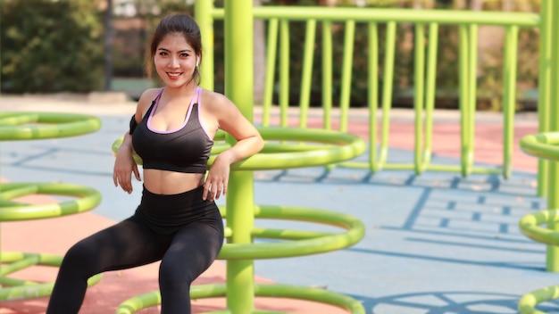 市の公共運動とライフスタイルのコンセプト、ワイヤレスイヤホンと携帯電話から音楽を聴き、ジョギングやカメラを見て休んでいるスポーツウェアの若い魅力的なアジアの自信のある女の子。