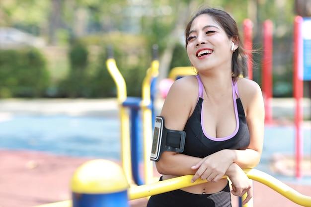 市の公共運動とライフスタイルの概念、ワイヤレスイヤホンと携帯電話から音楽を聴き、ジョギングと目をそらして休んでいるスポーツウェアの若い魅力的なアジアの自信のある女の子