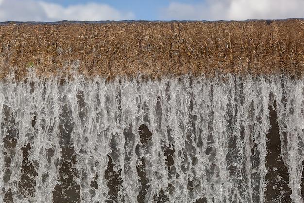 Городской речной водопад, крупный план большой каскадной стены в летний день, вид сбоку на падающий поток воды и водяную пену внизу
