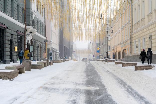 겨울 시즌 b에 차들이 있는 눈으로 덮인 도시 도로