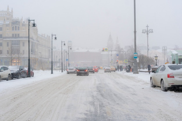 City road covered with snow with cars on the sidelines in winter season b