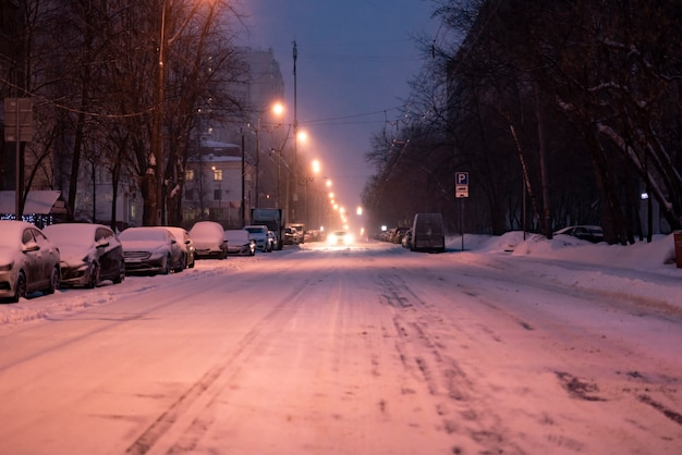 City road covered with snow with cars on the sidelines in winter season