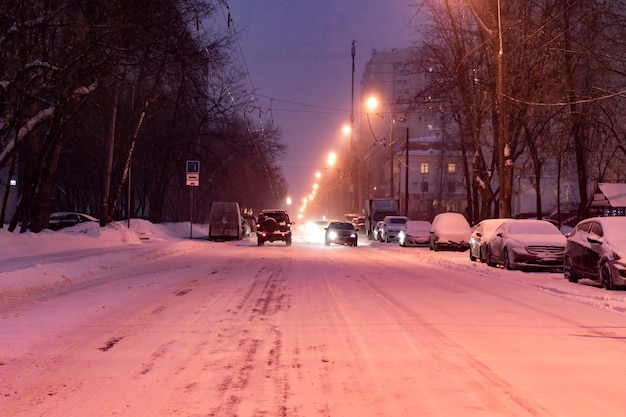 City road covered with snow with cars on the sidelines in winter season Premium Photo