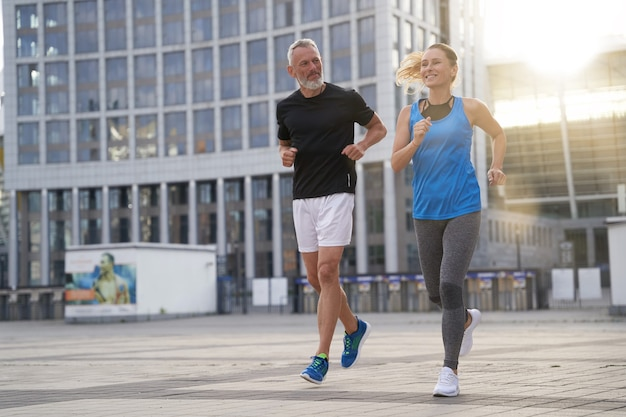City running middle aged couple jogging together in the morning while training outdoors
