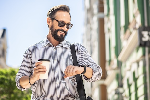 City rush. waist up of smiling adult man drinking coffee while checking time outdoors