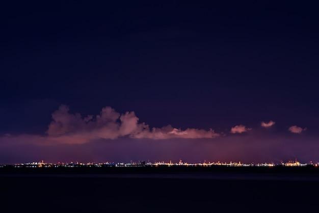 황혼의 하늘과 밤에 바다에서 도시 풍경