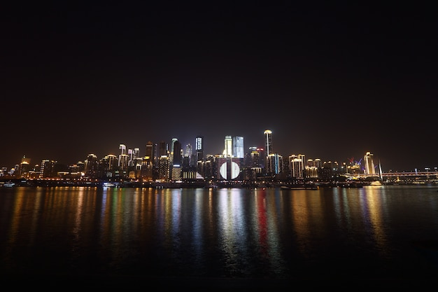 City scape of sky scrapper on river bank and reflect water and sky cloud in night time