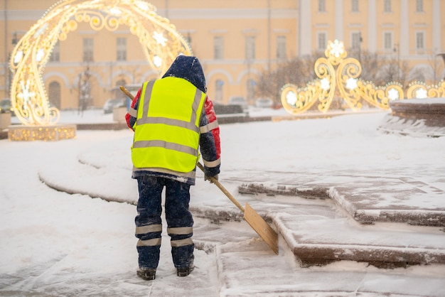 City service guy clean snow from streets with shovel b