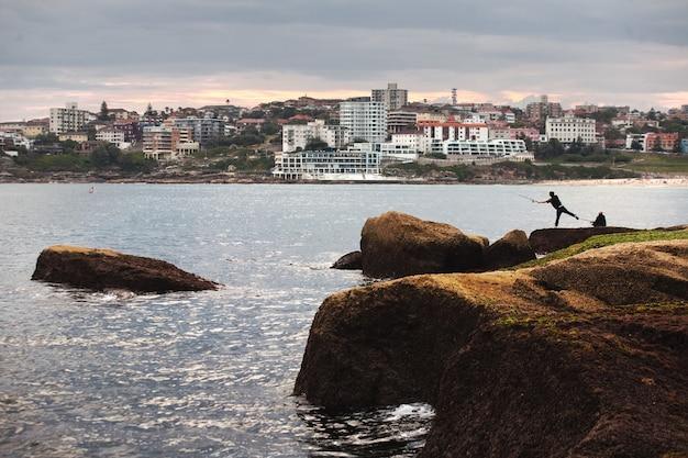 オーストラリアのボンダイビーチの岩の崖の上の街のスカイラインと漁師