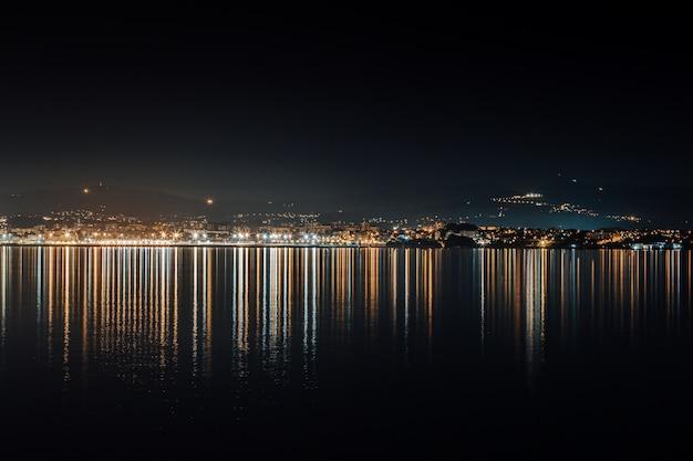 夜の間に海に反射する街のスカイラインライト