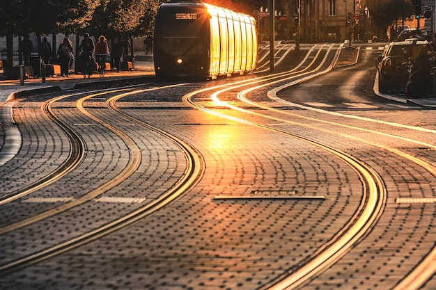 City street scene with tramway at sunset in bordeaux, france