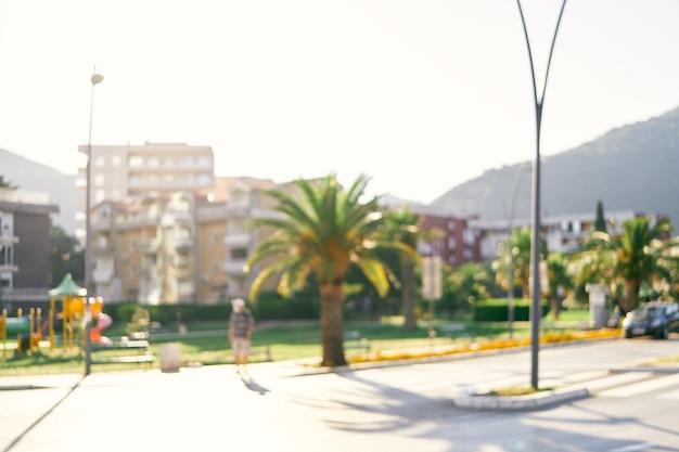 배경 흐림에 야자수 집과 산이 있는 도시 거리