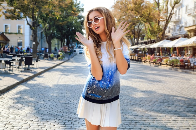 City stylish portrait of beautiful woman posing at the street ant nice sunny fall autumn day. wearing bright blue casual sweater and sunglasses. travel and having fun alone.