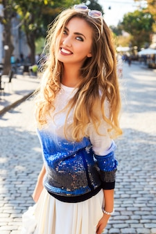 City stylish portrait of beautiful woman posing at the street ant nice sunny fall autumn day. wearing bright blue casual sweater and sunglasses.