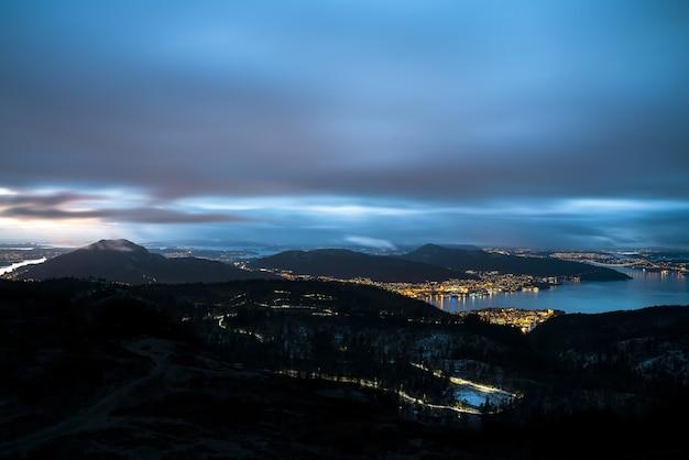 산으로 둘러싸인 도시와 저녁에 흐린 하늘 아래 빛으로 덮인 바다