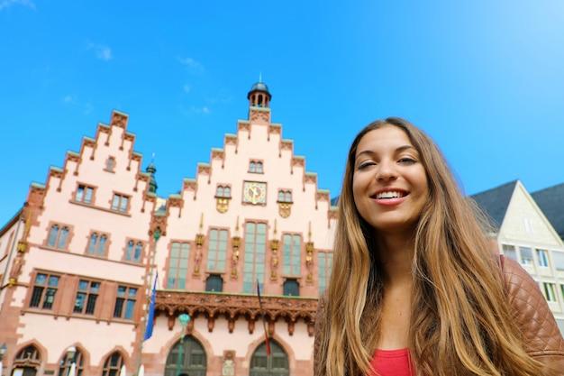 ドイツの都市観光ライフスタイル。フランクフルト旧市街を訪れる若い女性。レーマーベルク広場、フランクフルト、ドイツの観光女性の笑みを浮かべてください。