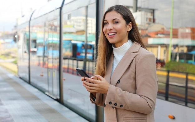 도시 교통. 트램 정류장에서 휴대를 들고 행복 한 아름 다운 여자. 웃는 비즈니스 우먼 스마트 폰을 통해 전기 전송에 대 한 지불 온라인 티켓 서비스에 만족.