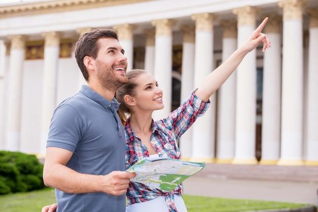 도시 여행자. 지도를 들고 있는 남자와 멀리 가리키는 여자가 있는 동안 아름다운 건물 근처에 서 있는 행복한 젊은 관광 커플