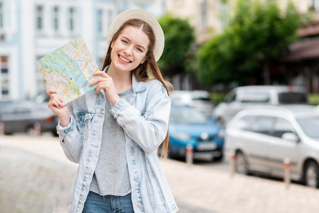 City traveller holding a map and smiles