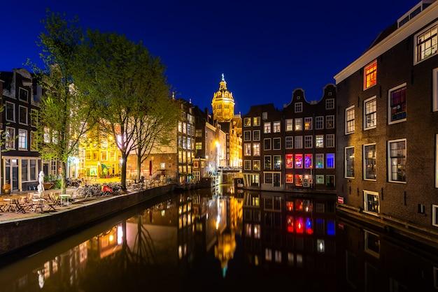 Вид на город амстердам, нидерланды с реки амстел ночью.