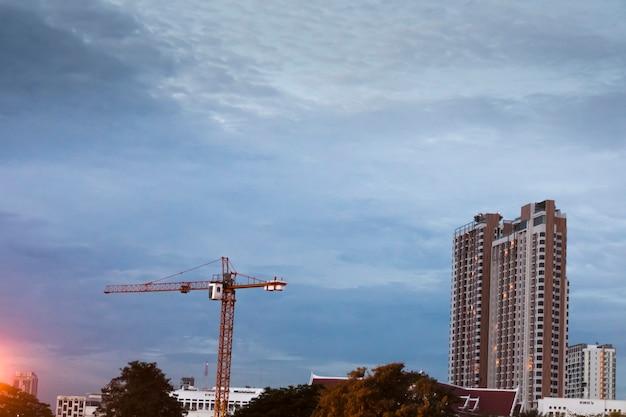 하늘과 구름을 배경으로 고층 건물과 크레인이 있는 도시 전망.