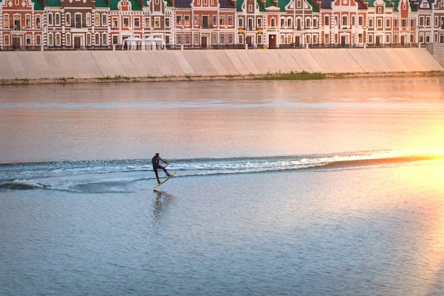 City wake surfer jumping on surface of river. wakeboarder dressed in swimsuit.