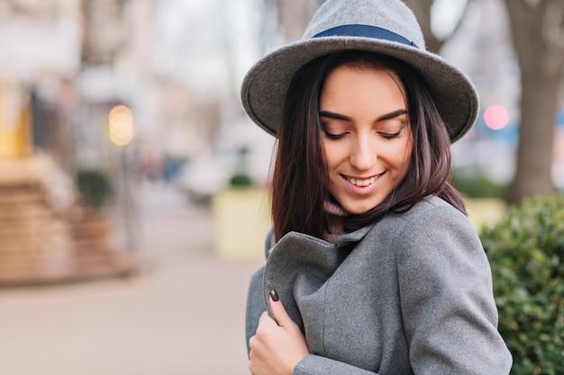 灰色のコートで魅力的なスタイリッシュな若い女性、都市の通りを歩いて帽子の都市散歩時間。目を閉じて微笑み、真のポジティブな顔の感情、贅沢なライフスタイル、エレガントな見通しを表現します。
