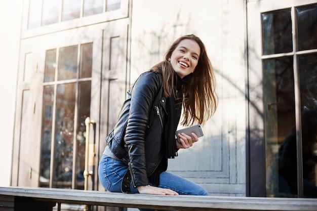 긍정적 인 시민과 도시. 가죽 자 켓 카페 근처에 앉아 벤치에 기대어 옆으로 보는 아름 다운 유행 여자