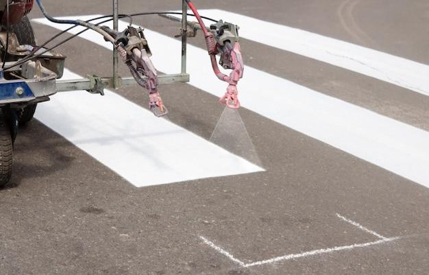 Городские рабочие красят пешеходные переходы на дороге. малярная машина рисует полосы на асфальте для пешеходов.