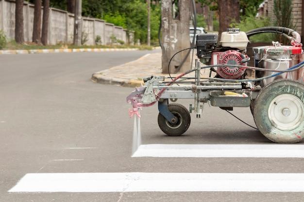 市の労働者は道路に横断歩道の車線を描きます。