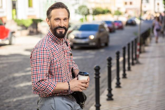 Городской жизни. веселый красивый мужчина-менеджер идет на работу, попивая кофе