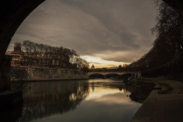 テヴェレ川の水とサンピエトロ大聖堂のドームの暖かい夕日の空の反射と古い橋の街並みとパノラマビュー