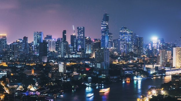 Cityscape of bangkok city skyline at night with light streaks of boat in thailand,