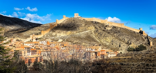 Cityscape of the city of albarracin with its medieval wall that surrounds the city above the mountain. teruel, spain. europe.