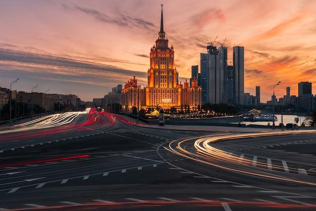 Городской пейзаж с небоскребом на проспекте с множеством автомобильных световых дорожек на фоне закатного неба