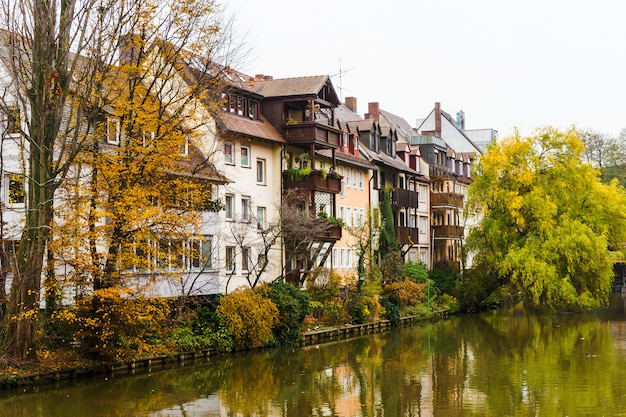 Cityscape from riverside in nurnberg, river pegnitz with living houses and trees in bavarian town, nuremberg, germany