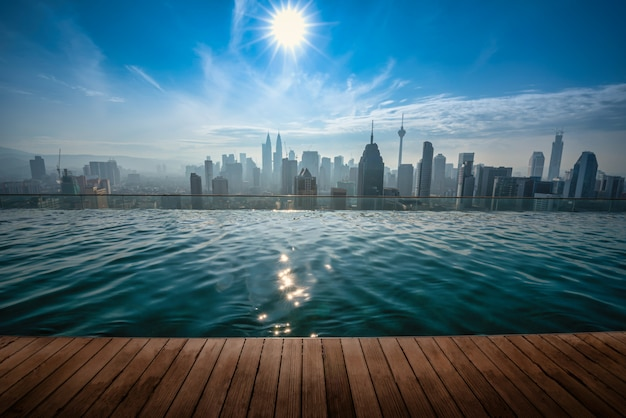 Cityscape of kuala lumpur city skyline with swimming pool on the roof top of hotel at daytime in malaysia.