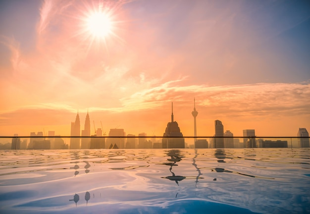 Cityscape of kuala lumpur city skyline with swimming pool on the roof top of hotel at sunrise in malaysia.