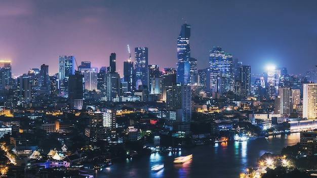 タイのボートの光の筋と夜のバンコクの街並みの街並み、