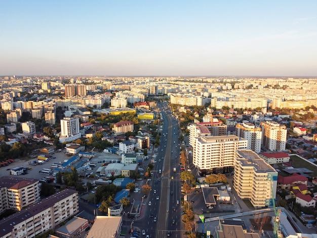 Городской пейзаж бухареста, дорога с движущимися автомобилями, несколько жилых домов, чистое небо, вид с дрона, румыния