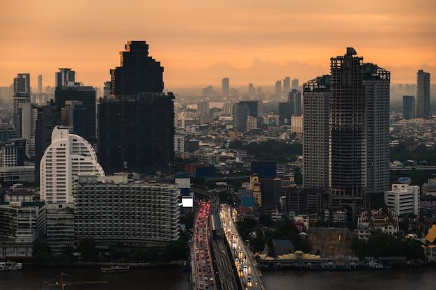 비즈니스 지구에서 monring에있는 다리에 자동차 소통량을 가진 건물의 풍경. 방콕, 태국