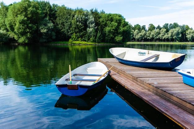 Городской пейзаж пустой лодки припаркован на берегу озера в парке в мегаполисе