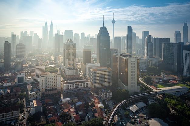 Городской пейзаж горизонта города куалаа-лумпур на голубом небе с солнечным светом в малайзии на дневном времени.