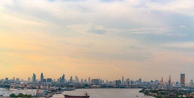 オレンジと青の空とモダンな建物と川の街並み。超高層ビル。都会のスカイライン。夕焼けの空と夕方の首都。繁華街の高層ビルが混雑しています。
