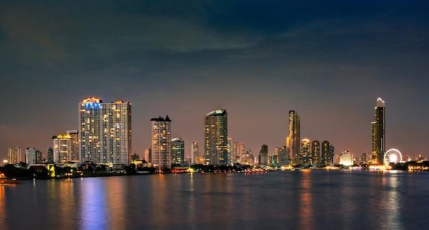 Городской пейзаж современного здания возле реки в ночное время. современная архитектура офисного здания. небоскреб с вечерним небом. черно-белые тона изображения.
