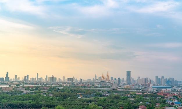 バンコクの高速道路とコミュニティのあるモダンな建物の街並み。高架橋を運転する車。超高層ビル。街の緑の木々。都市生活のための酸素。環境にやさしい街。都会のスカイライン。