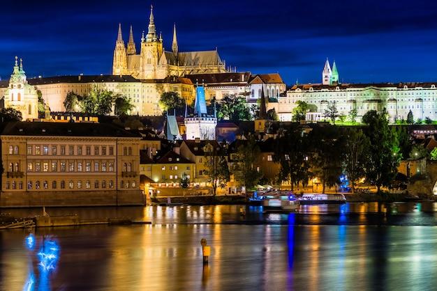 Городской пейзаж праги с замком, башнями и карловым мостом в ночное время. чехия.